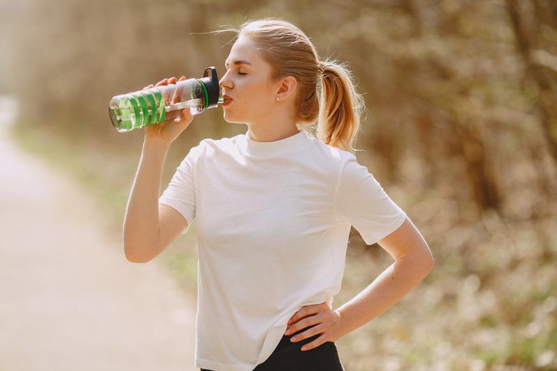 Torr hud på sommaren - kvinna som dricker vatten